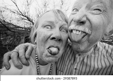 Closeup portrait of crazy elderly couple outdoors sticking out tongues