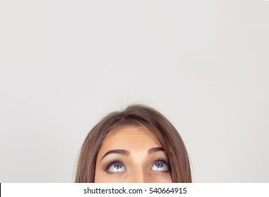closeup portrait cropped image half face eyes of woman looking up white grey wall background with copy space for text above head. Human face expression, emotions, feelings, body language