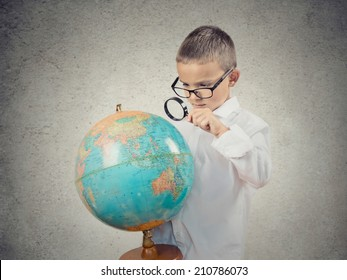 Closeup portrait curious child holding earth globe map in his hand, looking through magnifying loupe, picking his next destination isolated grey wall background. Human facial expression.Travel concept