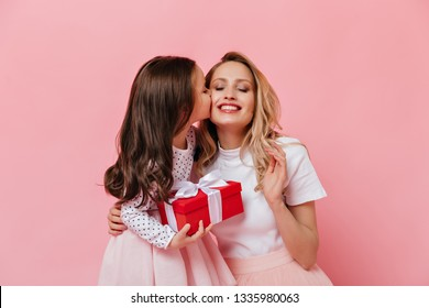 Close-up portrait of curly female child kissing mom. Girl makes surprise to her older sister
