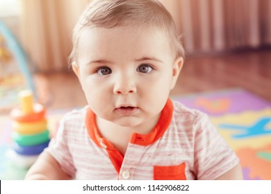 Closeup portrait of cute adorable blond Caucasian smiling child boy with blue eyes sitting on floor in kids children room. Little baby playing with toys on playmat. Early education development