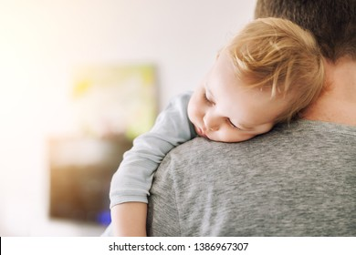 Close-up portrait of cute adorable blond caucasian toddler boy sleeping on fathers shoulder indoors. Sweet little child feeling safety daddys hand. Responsibility and childcare. happy childhood