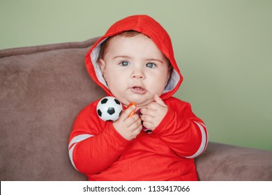 Closeup portrait of cute adorable Caucasian baby boy, wearing red sport hoodie shirt. Seven months child sitting on couch and holding football soccer toy