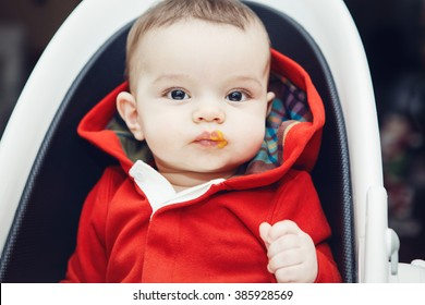 Close-up portrait of cute adorable Caucasian little baby boy with dark black eyes sitting in high chair in kitchen looking in camera eating meal puree