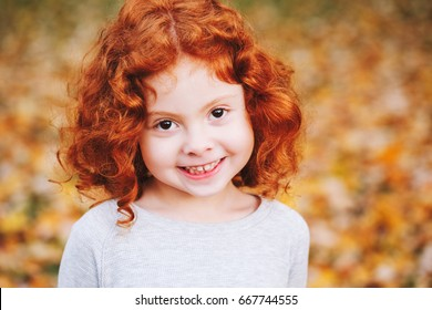 Closeup portrait of cute adorable smiling  little red-haired Caucasian girl child standing in autumn fall park outside, looking in camera, happy lifestyle childhood concept