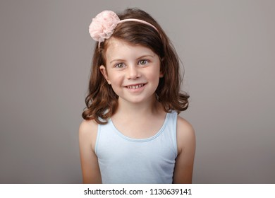 Closeup portrait of cute adorable white brunette Caucasian preschool girl making faces in front of camera. Child smiling laughing posing in studio on plain light background. Kid expressing emotions