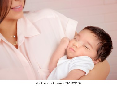 Closeup portrait of cute arabic newborn baby on mothers hands, happy young family, innocent child, new life concept