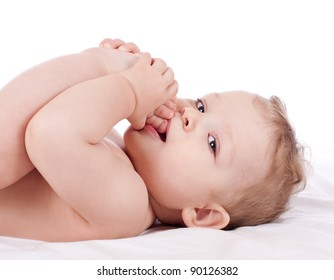 Closeup portrait of cute baby boy taking his feet in his mouth on white background