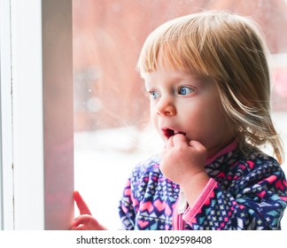Close-up Portrait of Cute Blonde 18 Month Old Toddler Girl with Big Blue Eyes, looks at the window, sucking fingers, Sweet Face Expression, Stand by the Window, Snowy Background