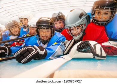 Close-up portrait of cute boys in protective equipment, laying on ice hockey rink, smiling and looking at camera