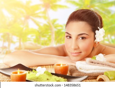 Closeup portrait of cute brunet girl lying down on massage table outdoors, tropical beach, luxury spa resort, alternative therapy, summer relaxation concept