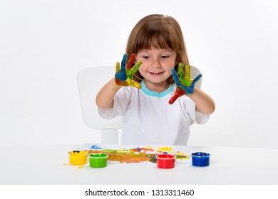 Close-up portrait of a cute cheerful happy smiling little girl draws her own hands with gouache or finger paints isolated on white background