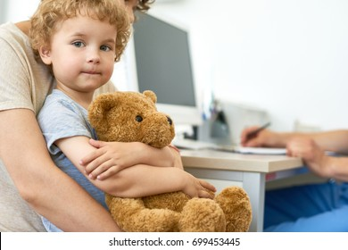 Closeup portrait of cute child sitting on mothers lap in doctors office waiting for check up hugging plush teddy bear toy