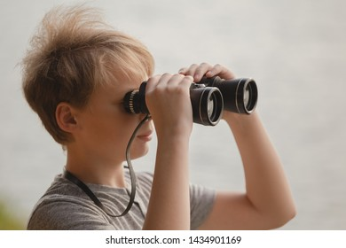 Closeup portrait of cute curious kid exploring nature using old vintage binoculars. Boy isolated on blurry river water background. Horizontal color photography.