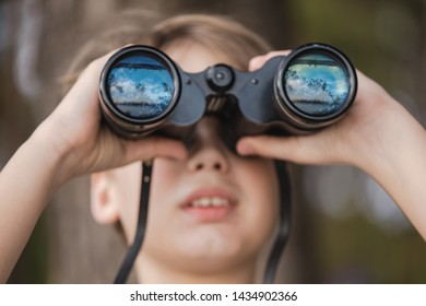 Closeup portrait of cute curious kid exploring nature using old vintage binoculars. Beautiful blue sky, river and nature reflected in glass of lenses. Horizontal color photography.