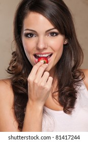 Close-up portrait of a cute female eating a fresh strawberry