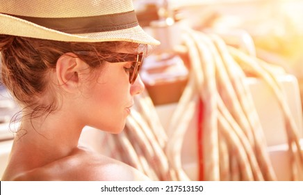 Closeup portrait of of cute female relaxing on the yacht in mild sunset light, side view of attractive woman wearing stylish hat and sunglasses, summer vacation concept