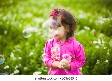 Closeup portrait of cute funny three years old baby playing outdoors in beautiful green field in countryside. Smiling little girl behind many soap baubles. Horizontal color photography.