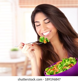 Closeup portrait of cute girl eating salad on the kitchen, enjoying fresh tasty vegetables with closed eyes, healthy lifestyle concept