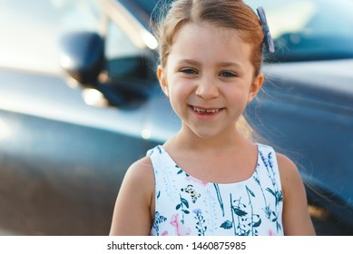 closeup portrait of cute girl in floral dress at car