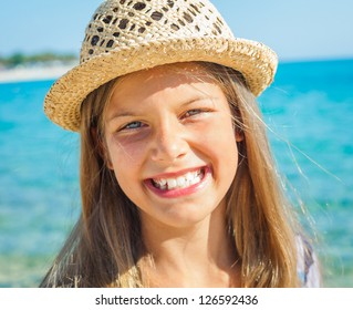 Closeup portrait of cute girl in hat on the beach