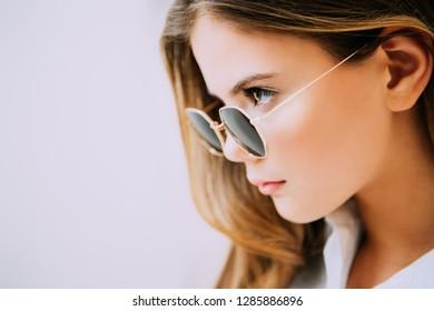 Close-up portrait of a cute girl teenager with sunglasses on the white background. Glasses for a modern young generation. Beauty, fashion.