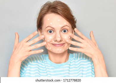 Close-up portrait of cute happy girl without makeup, smiling, with white drops of face cream on skin, over gray background. Care for imperfect, problem, acne prone skin. Skincare and beauty concept