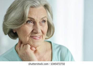 Close-up portrait of cute happy senior woman posing