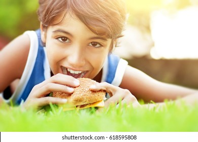 Closeup portrait of a cute happy teen boy lying down on green grass and eating delicious burger, enjoying tasty lunch outdoors, happy time at summer camp