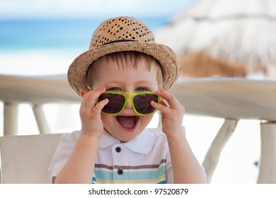 Closeup portrait of a cute happy toddler boy playing with sunglasses on a tropical beach