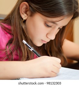 Close-up portrait of a cute hispanic girl writing on her school notebook