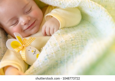 Closeup portrait of a cute little baby sleeping with decorative egg toy, traditional symbol of Easter holiday, love and religion concept