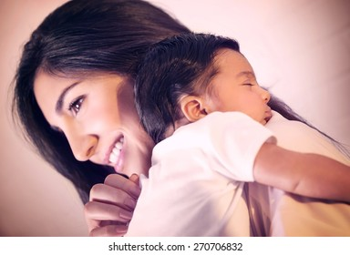 Closeup portrait of cute little baby sleeping on mothers shoulder, happy young loving family, new life concept