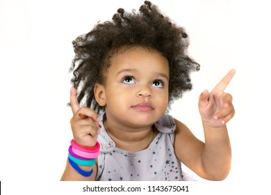 Close-up portrait of cute little child looking and pointing with fingers. Lovely dark curly hair. Sweet baby wearing colourful bracelets. Isolated on white background