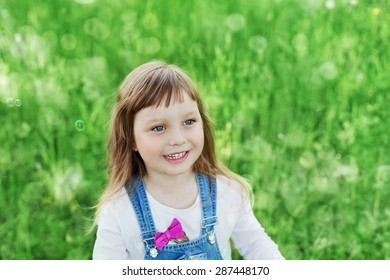 Closeup portrait of cute little child girl or kid standing on a green meadow and laughs, happy childhood