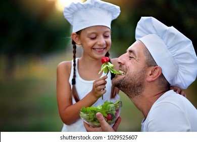 Closeup portrait of cute little girl with her father eating salad together