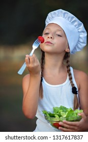 Closeup portrait of cute little girl eating salad