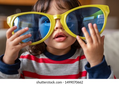 Closeup portrait of a cute little girl sitting in her living room at home wearing funny oversized novelty sunglasses