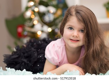 Close-up portrait of a cute little girl lying in front of Christmas tree