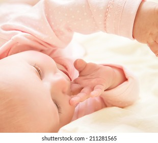 Closeup portrait of cute little newborn baby wearing pink clothes and sleep at home, day dreaming, innocence and tenderness concept