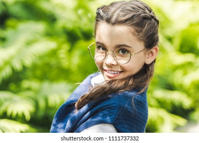 close-up portrait of cute schoolgirl in white shirt and jumper over shoulders looking at camera through stylish eyeglasses