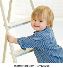 Closeup portrait of a cute smiling boy climbing the ladder