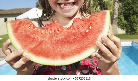 Closeup portrait of a cute smiling girl eating watermelon against swimming pool
