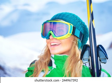 Closeup portrait of cute smiling skier girl wearing sportive mask and holding in hands ski, active winter vacation, happiness and enjoyment concept