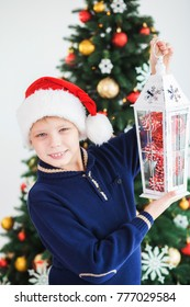 Closeup portrait of cute smiling teenage boy of 10 year old holding winter lantern with red Christmas baubles inside of it. Smiling kid isolated at festive tree background. Vertical color photography.