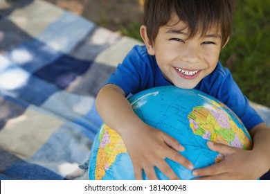 Close-up portrait of a cute young boy holding globe at the park