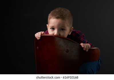 Close-up portrait of a Cute, young, frightened child hides behind a chair against black background and looking at camera. Human emotion, facial expression.