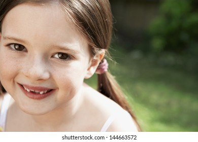 Closeup portrait of cute young girl smiling in park