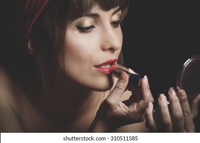Closeup portrait of cute young girl putting red lipstick on