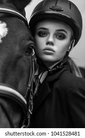 Closeup portrait of cute young woman and hourse. Indoor shot, sport and fashion concept.